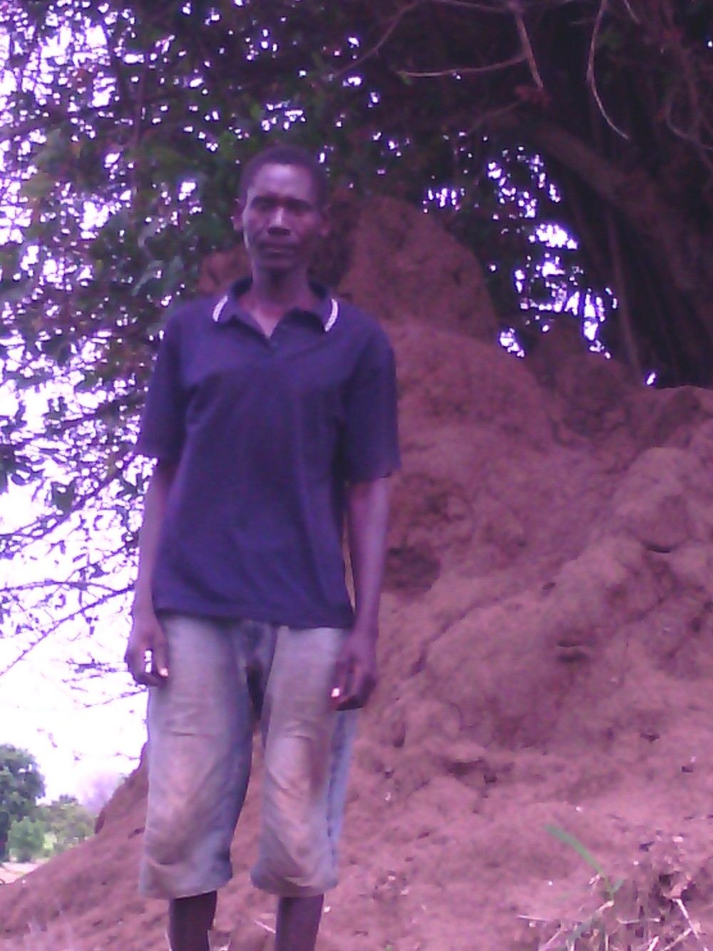 Standing by the termite mound where all his belongings were swept away.