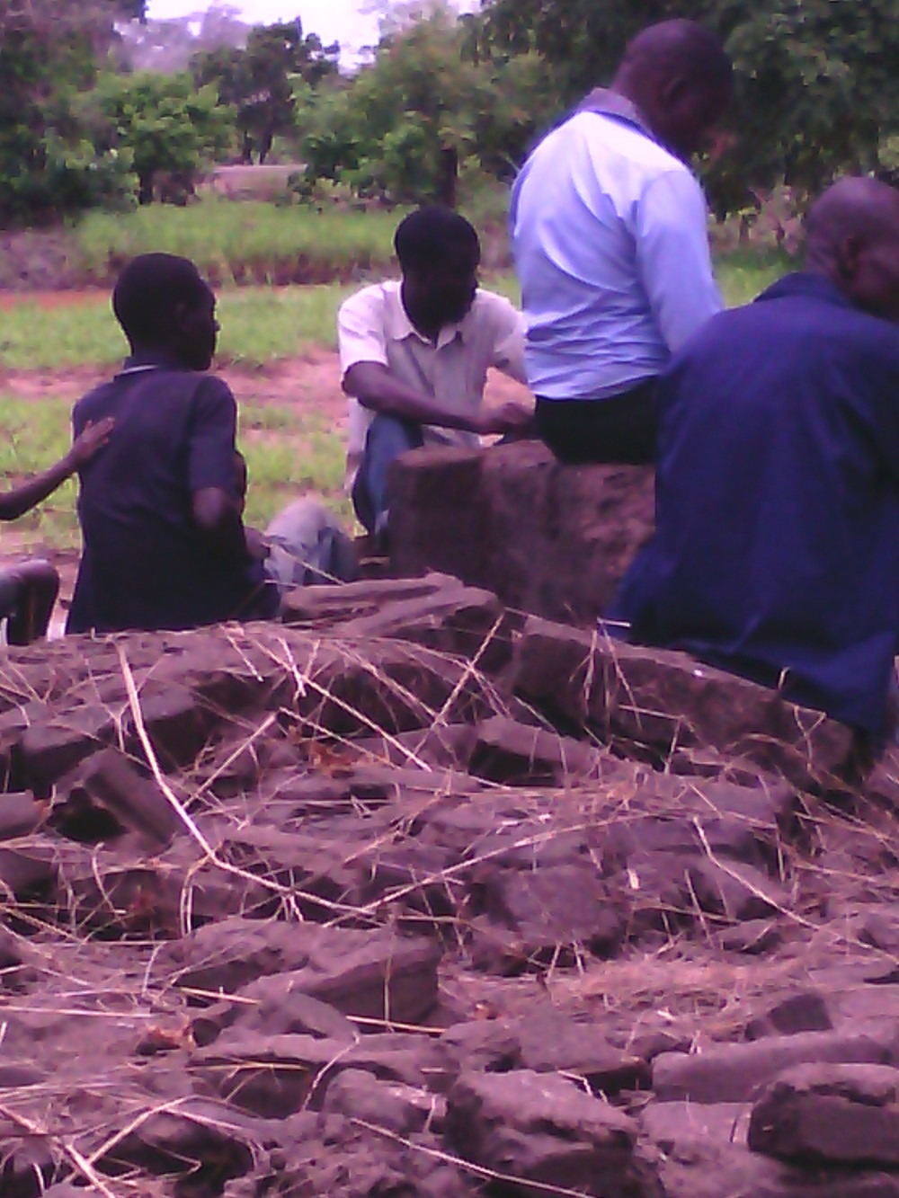 Mr. Mbota (in purple), sitting with the family on what USED to be the families home, now completely destroyed by the flood.