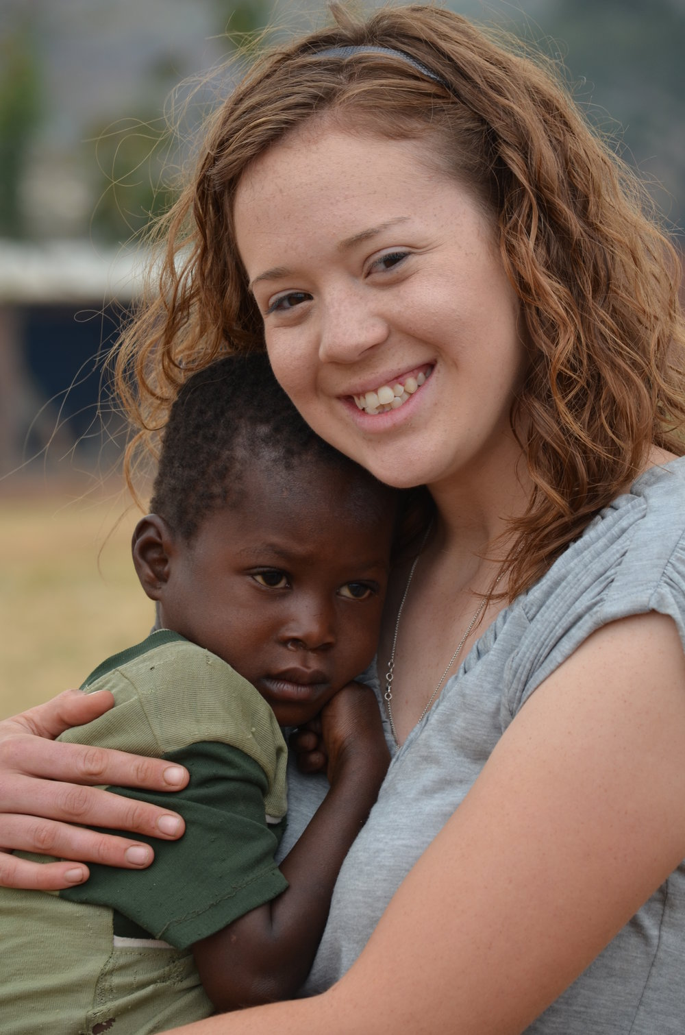 Kaitlyn Miller, 2011, holding another child with severe anemia.