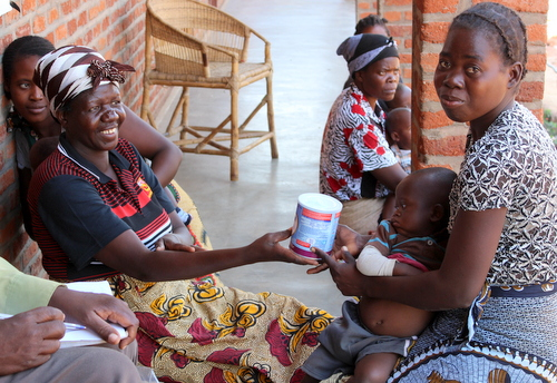 Mrs. Bokho distributing formula for infants whose mothers have lost their breastmilk supply due to illness or malnutrition.