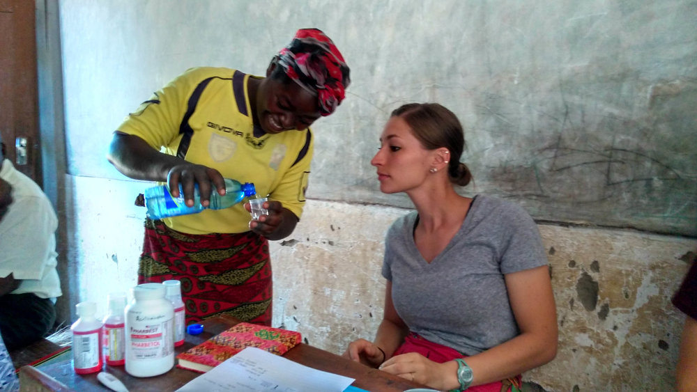 Karly Glibert teaching house mothers from TImothy's and Patricia's Homes to measure liquid medicines for treating fevers.