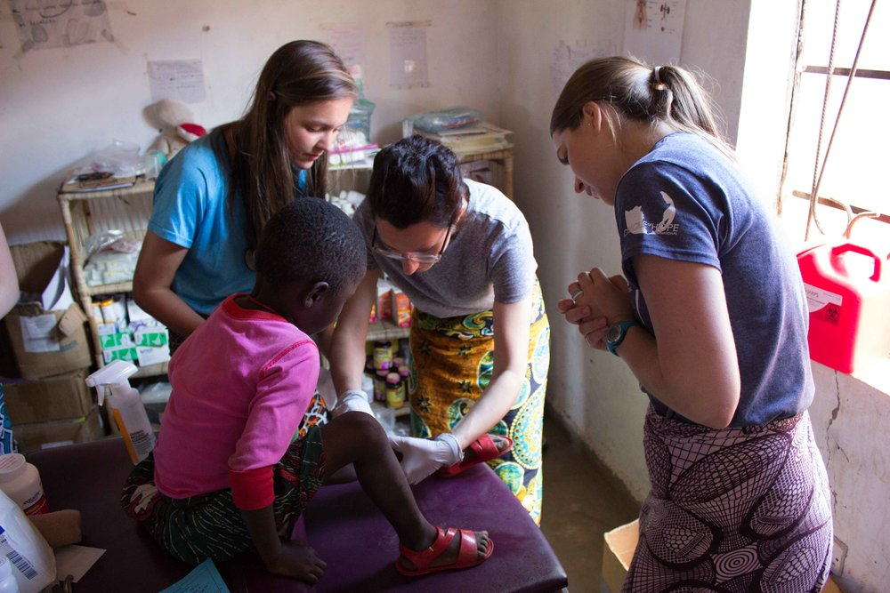 Hannah Yoder, Liesel Ratliff and Lindsey Draper work together in the clinic to care for a child.