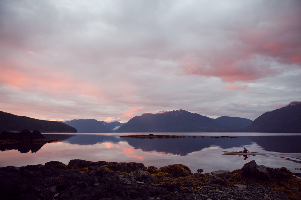 Adam Andis paddles during sunset.  South Baranof Island, Alaska.