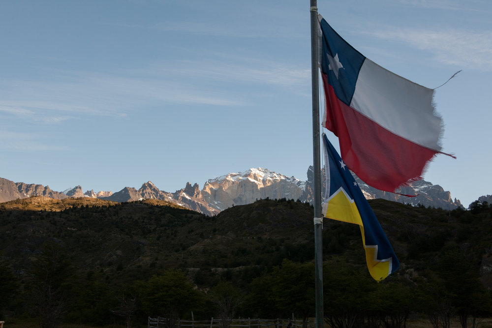 The national flag of Chile, and the flag for Patagonia flutter in the evening air.  The breeze was calm this night, but the frayed edges on the flag make me think that the winds get strong in this region - each fiber shaped by the pull of the current of air.