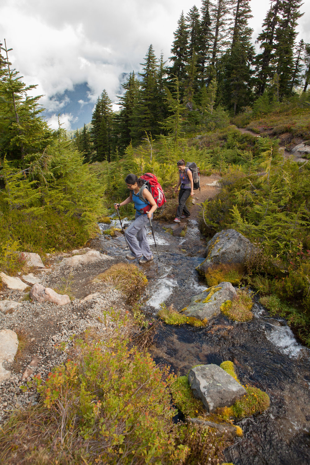 Backpackers cross a small stream on a loop hike through the Seattle Park section of Mount Rainier National Park in Washington.
