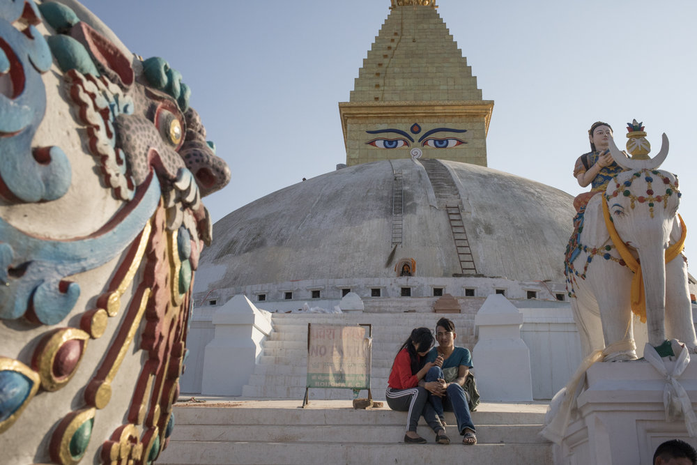A couple shares a moment on the steps of the Boudhanath Stupa.