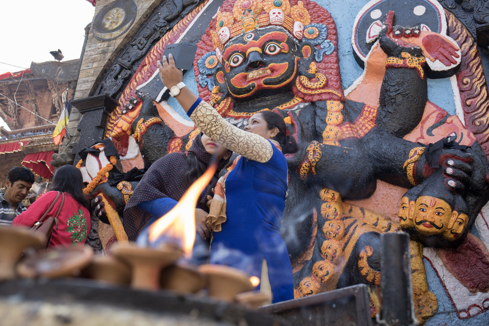 A butter lamp burns in the foreground as two women take a selfie in front of Kala (Black) Birabi in Durbar Square.