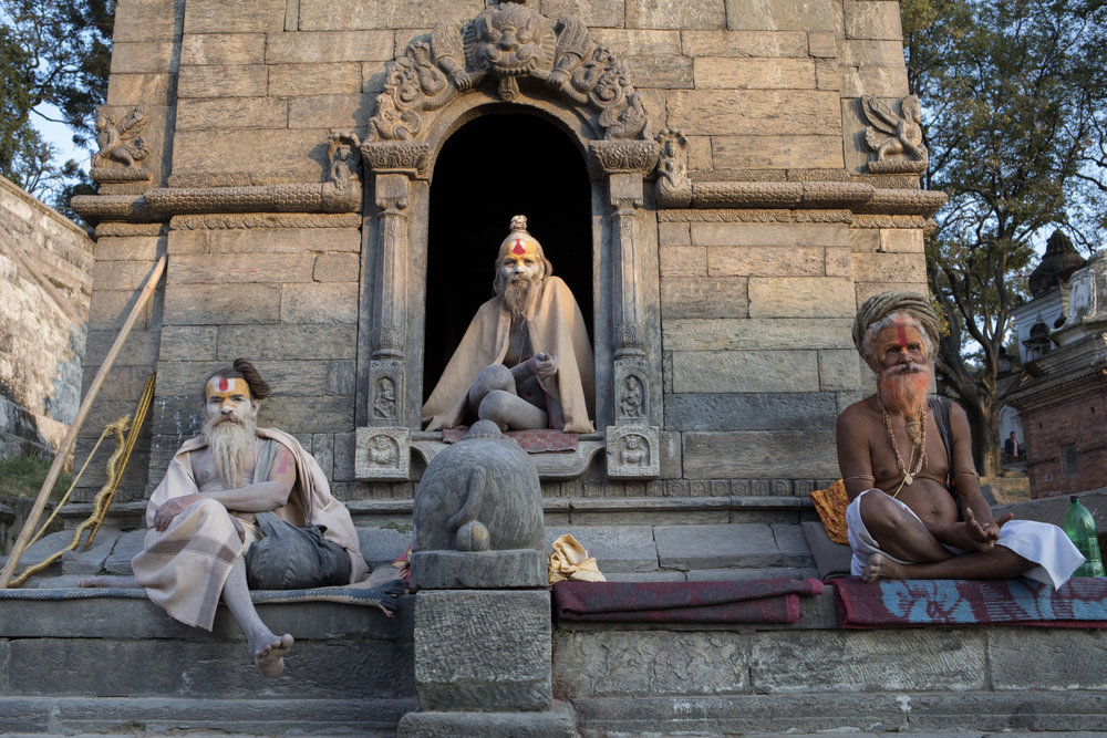 Sadhu Hindu holy men resting at Pashupatinath near the open crematorium along the Bagmati river.