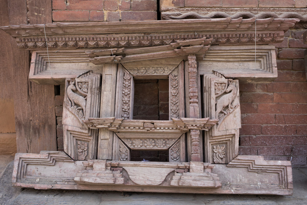 A hand-carved wooden window frame awaits repair.