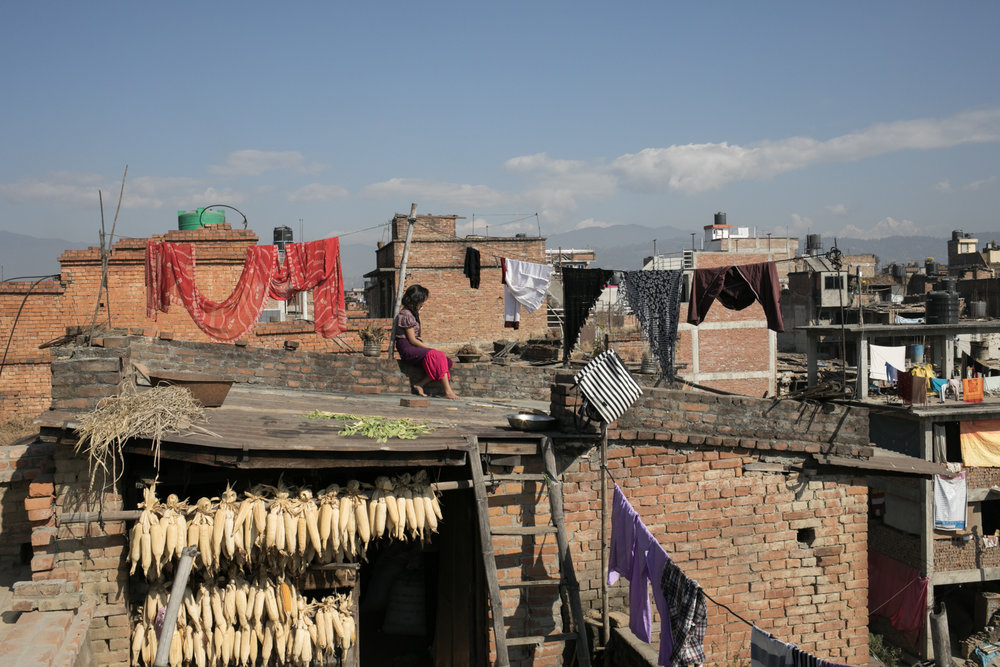 A girl sits atop a roof as clothing dries on the line.