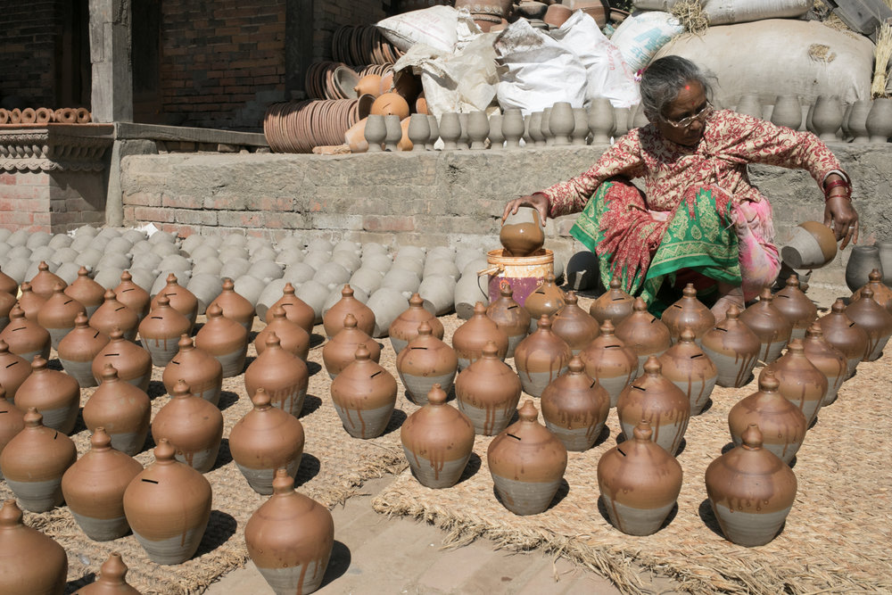 A woman adds color to ceramic coin jars.