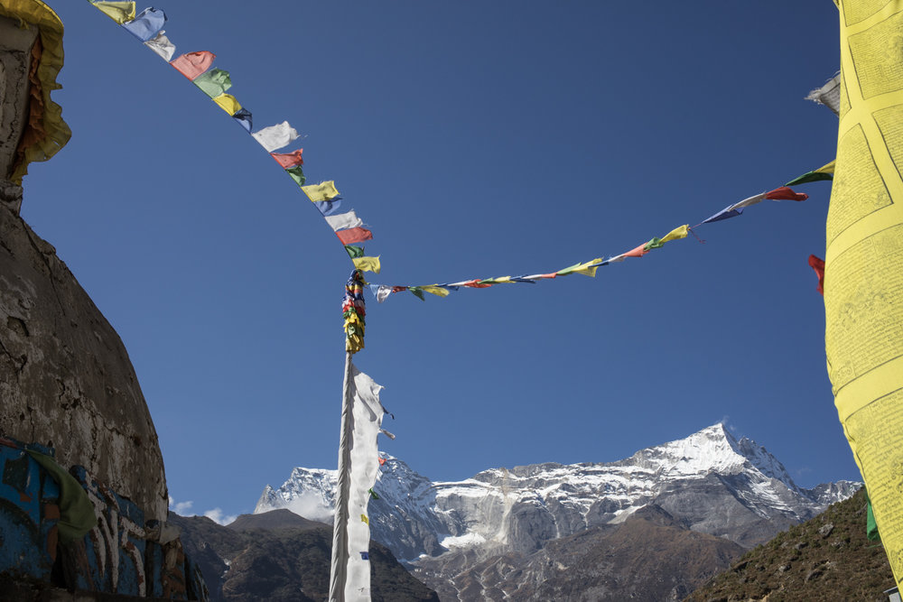 Prayer flags fly in the wind with Kongde Ri in the background.