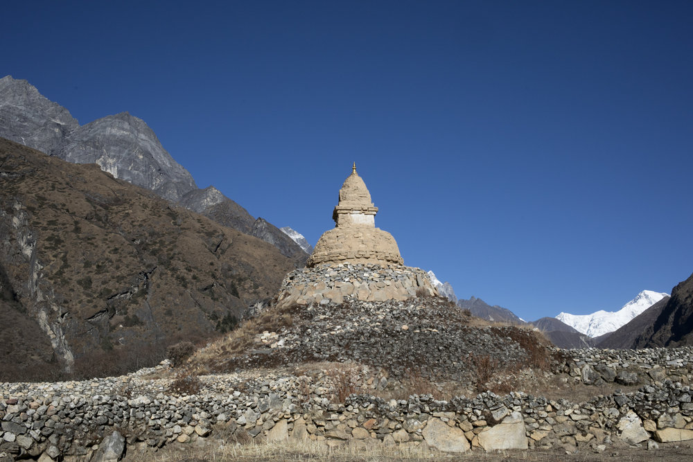 Stupa aged by the wind and winters stands at the edge of Phortse.  In the background, you can see Cho Oyu, the sixth highest mountain in the world.  Cho Oyu, China, 8,201 m / 26,906 ft.  (Peakfinder).