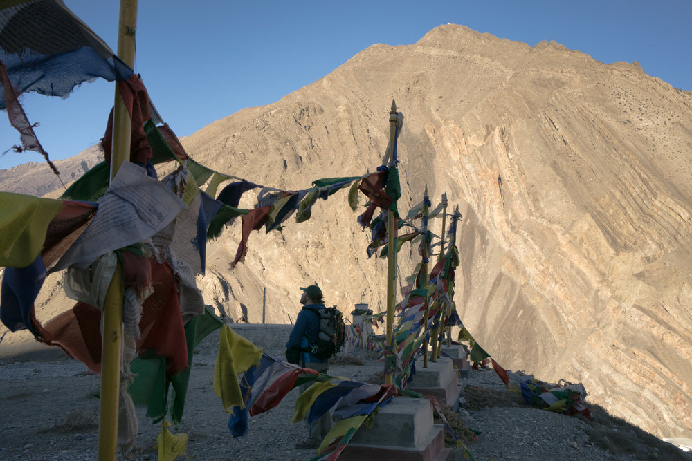 Aaron stands on a ridge with Prayer flags as the morning sun spreads across the distant peak.