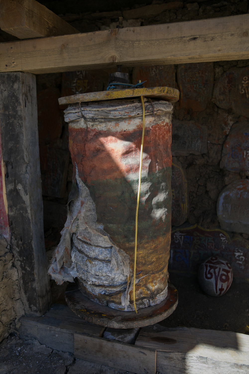 An ancient prayer wheel that is split. You can see the rounds of cloth that fill the inside of a prayer wheel with prayers written across the fabric.