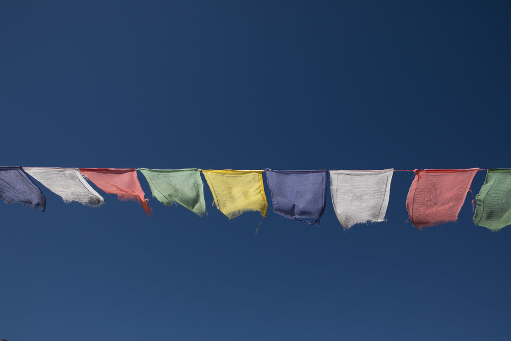 Prayer flags flutter in the wind.  Each strand that releases from the flag is considered a prayer being let out to the world.