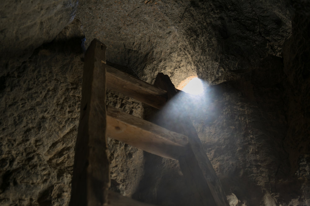 A beam of light coming from a window in the upper level highlights dust in the air.  The cave system is a series of rooms joined by hallways and multiple levels now accessed by ladders. I was surprised by the number of rooms in this dwelling. You can still see marks on the rocks where the caves were carved many years ago.