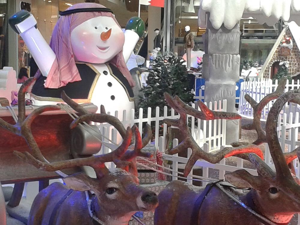 Arab snowman and a reindeer pulled sleigh.