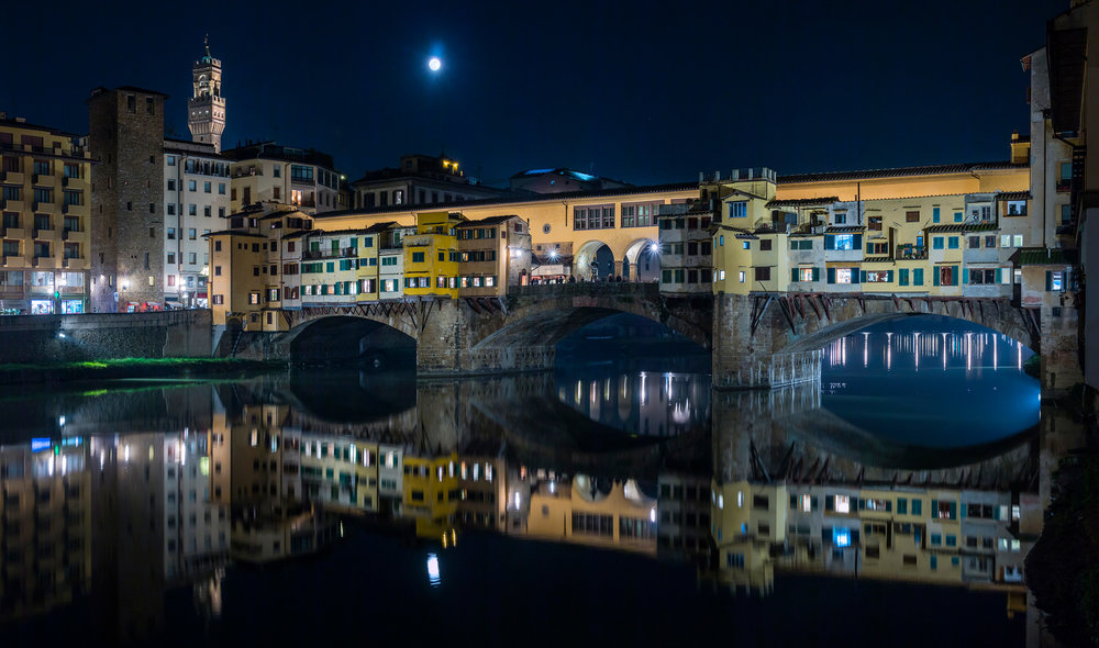 Florence, Italy: Ponte Veccho by night, with the tower of Palazzo Vecchio and the full moon in the background