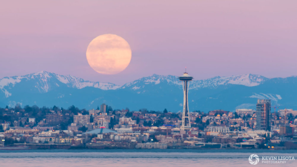 Moonrise over Seattle and the Cascade Mountainss ruined by strong heat distortion when cold air above the waters of Puget Sound mixed with warm air on a summer-like winter afternoon. 500 mm, 1/3 sec, f/10, ISO 80.