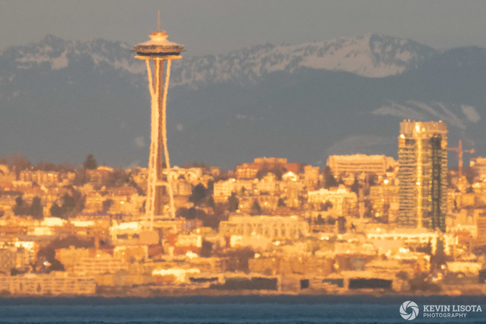Strong heat distortion of Seattle skyline taken from over 7 miles of water. Air temperature ~ 75 °F, water temperature ~47 °F. 500 mm, 1/400 sec, f/9, ISO 1250.