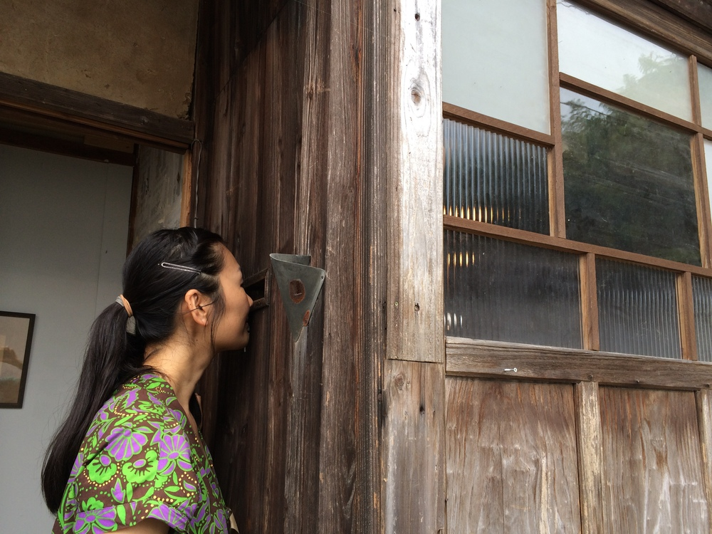 Aya peaking in the mail slot of the old house we'll be showing in. 郵便受けから中を覗く。