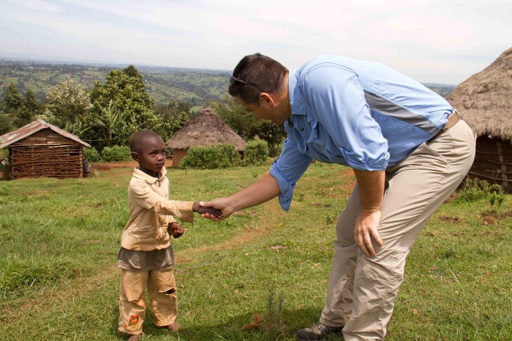 Keith Forwith shaking hands with Kenyan child
