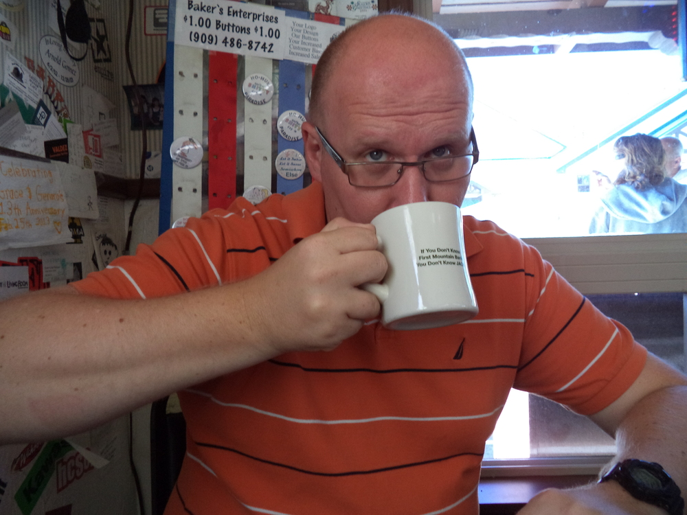 Dan drinking coffee out of a First Mountain Bank mug.