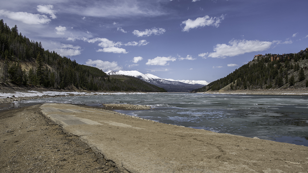 The road which led to the old town of Dillon, now permanently submerged under Dillon Reservoir. The photo shows the Snake River Arm of Dillon Reservoir, with Summerwood Estates on the right and the Gore Range in the distance. Swan Mountain Road, the thoroughfare between Keystone and Breckenridge, climbs the slope on the left.