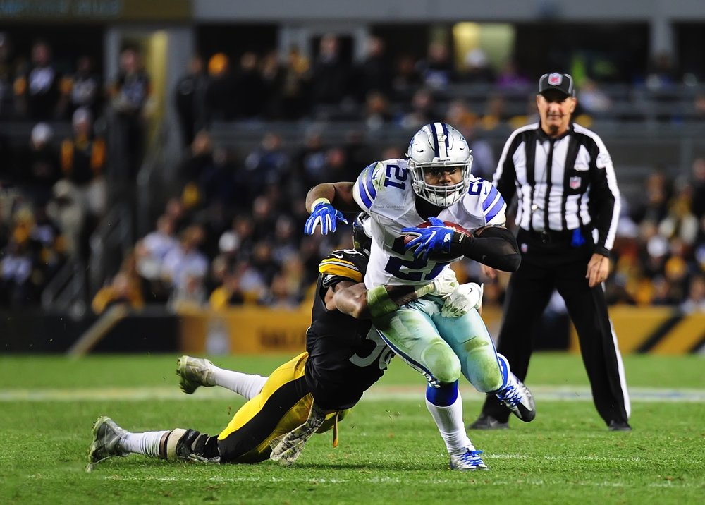 Ezekiel Elliott finishing a strong run against the Steelers defense.