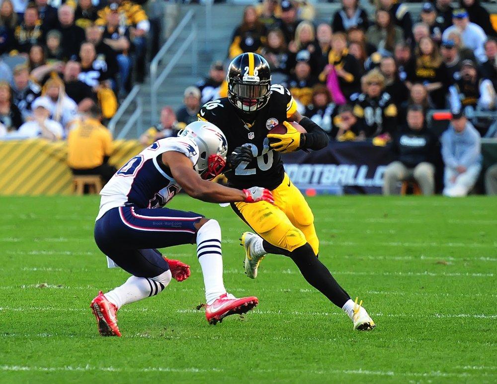 Bell running over a Patriots defender