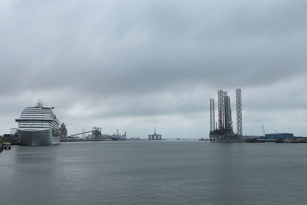 View down the channel. Carnival Cruise ship is docked and a semi-submersible and two-jack ups in for work.