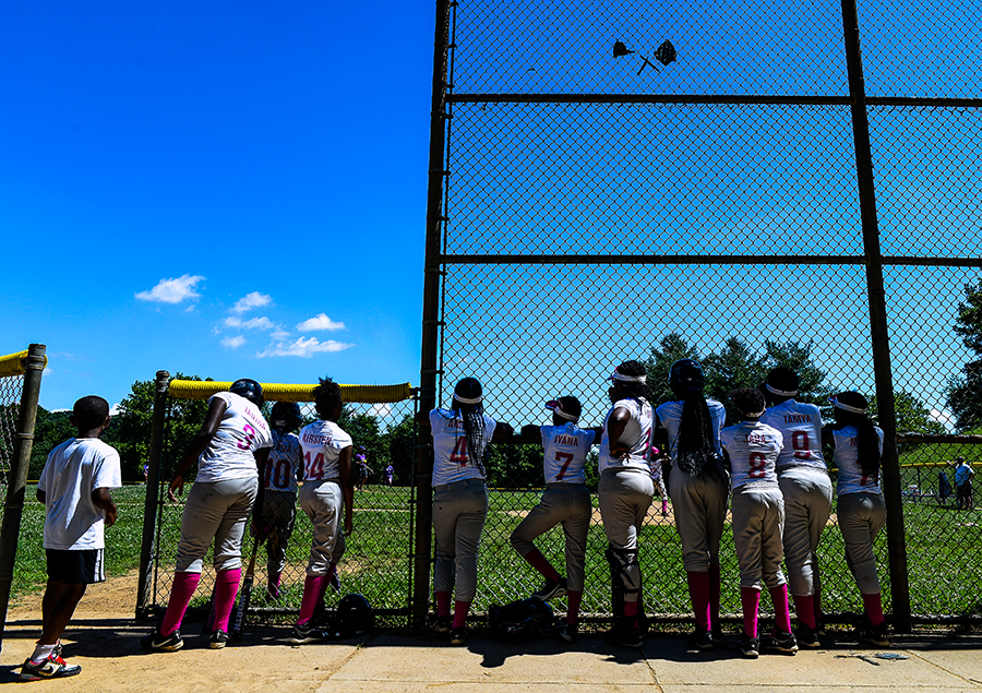 The Lady Doves softball team cheers on their teammate at bat.