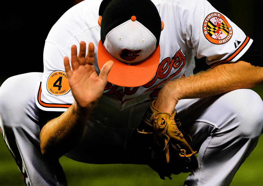 Baltimore Orioles pitcher Chris Tillman slams the ground in frustration after missing an out on Sept. 24, 2013 in Baltimore, Md.