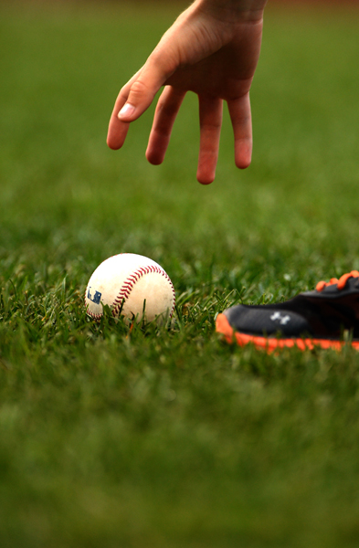 Orioles bat boy Andrew Guinart grabs for a ball during a home game on August 19, 2013 in Baltimore, Md.