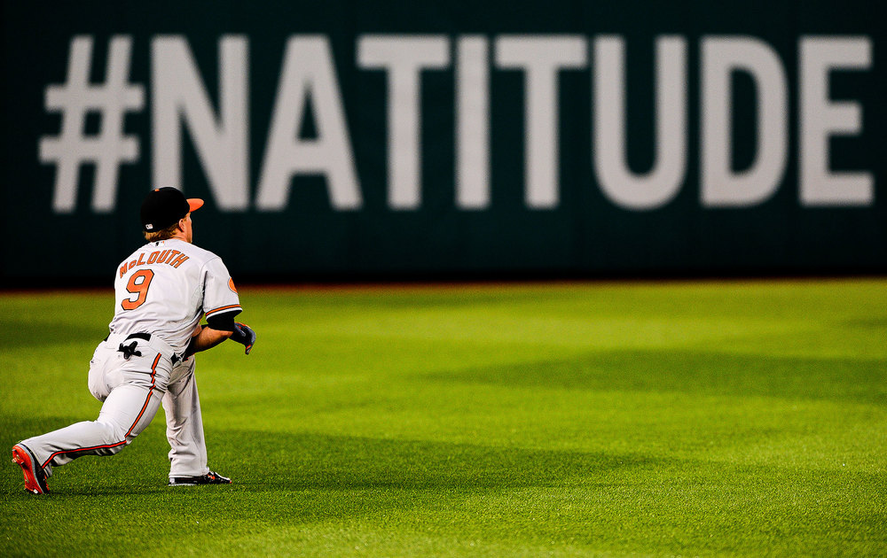 Nate Mclouth, Baltimore Orioles left fielder warms up during game against the Washington Nationals at National Park on June 29, 2013 in Washington, D.C.