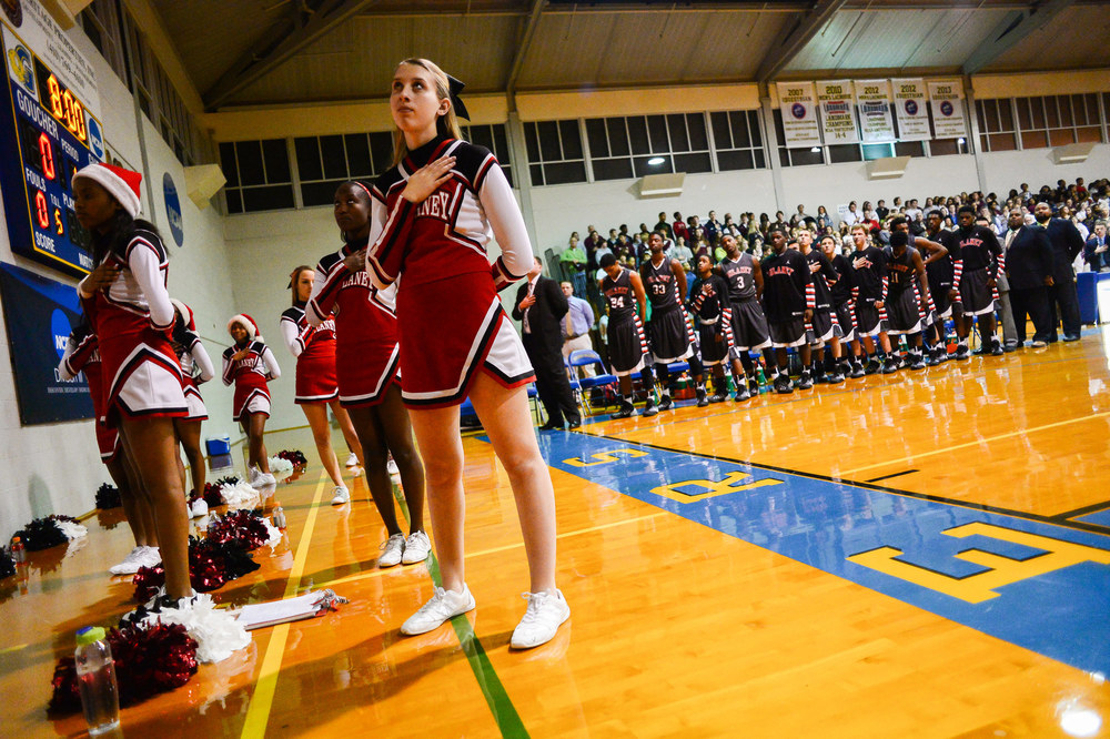 Dulaney High School cheerleaders and basketball players observe the national anthem before their game on Dec. 18, 2013.