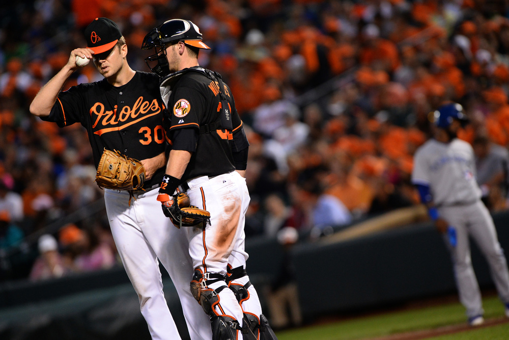 Baltimore Orioles pitcher Chris Tillman talks with catcher Matt Wieters on July 12, 2013 at Oriole Park at Camden Yards in Baltimore, Md.