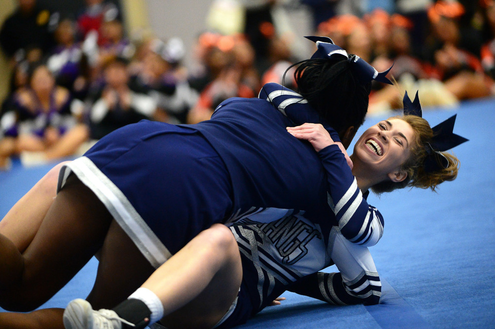 Marriotts Ridge junior Jacklyn Spano, back, falls to ground while embracing senior Danielle Boteng after the completion of their routine.