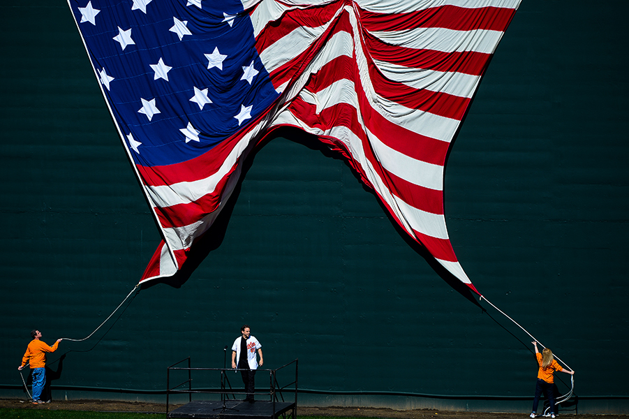 Richard Troxell of Thurmont, Md. prepares to sing the national anthem while an American flag is dropped behind him prior to the start of opening day at Oriole Park at Camden Yards on March 31, 2014.