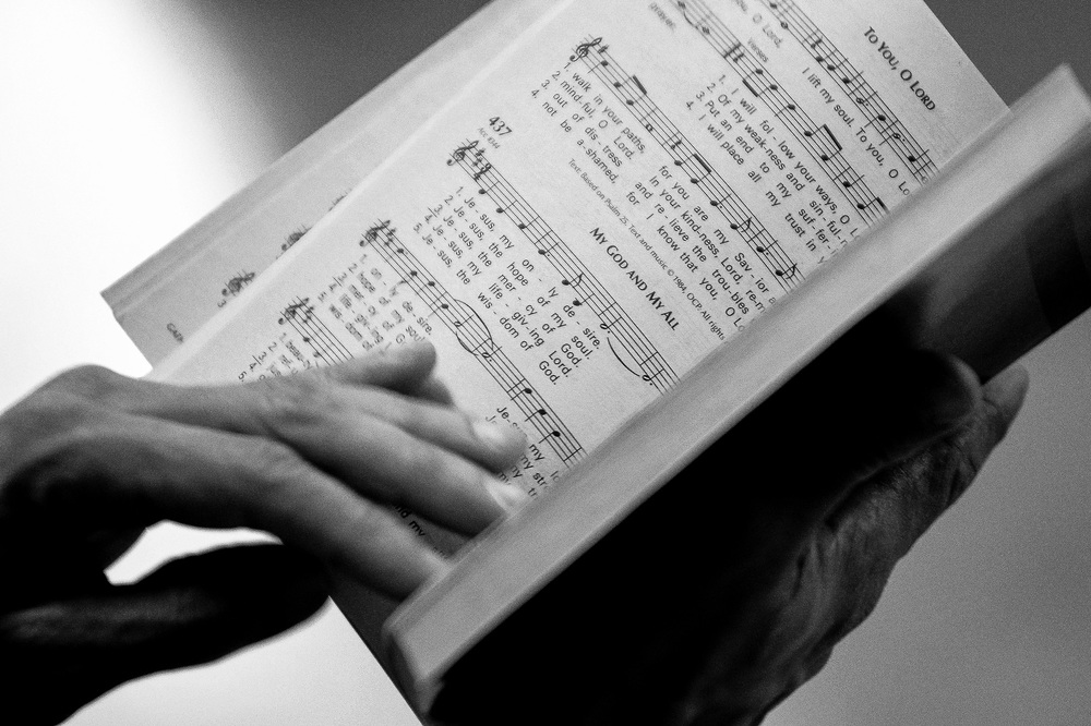 A member of the congregation reads from sheet music during the fifth Sunday of Lent service at Saint Charles of Brazil Parish on April 6, 2014 in Arbutus, Maryland.