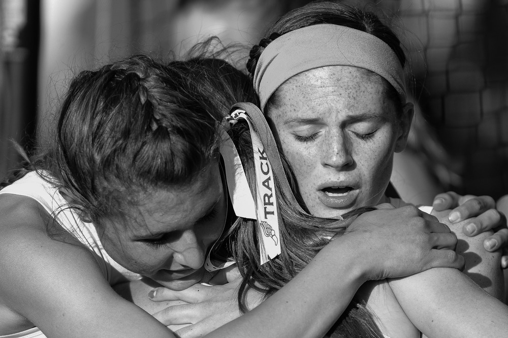 Jennifer Bleakney, left, and Olivia Healey, right, embrace Rebekah Markovitz all of Atholton High School after winning the 4x400 meter relay on the second day of the Howard County Track Championships at Wilde Lake High School in Columbia, Maryland on May 6, 2014.