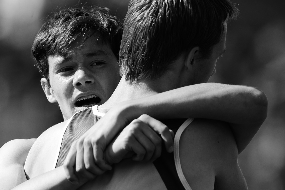 Toby Dilworth of Glenelg High School grabs ahold of a competitor after completing the boys 1600 meter race on the second day of the Howard County Track Championships at Wilde Lake High School in Columbia, Maryland on May 6, 2014.