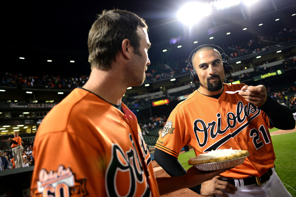 J.J. Hardy of the Baltimore Orioles, left, offers some pie to Nick Markakis of the Baltimore Orioles after a game against the Kansas City Royals on April 26, 2014 in Baltimore, Maryland.