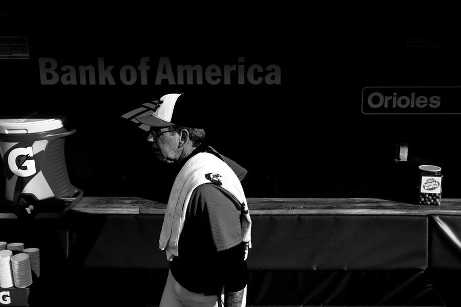 Baltimore Orioles pitching coach Dave Wallace walks through the dugout prior to the start of a MLB game against the Texas Rangers on June 30, 2014 at Oriole Park at Camden Yards in Baltimore, Maryland.