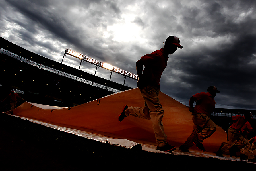 Members of the Baltimore Orioles grounds crew pull the tarp off of the field after the conclusion of a rain delay during a MLB game between the Baltimore Orioles and the Texas Rangers at Oriole Park at Camden Yards in Baltimore, Maryland on July 3, 2014.