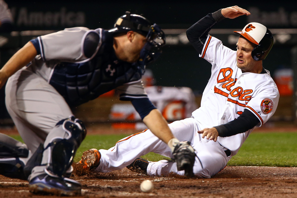 Catcher Caleb Joseph, right, of the Baltimore Orioles slides safely into home past catcher Brian McCann of the New York Yankees during a MLB game at Oriole Park at Camden Yards on April 12, 2015 in Baltimore, Maryland.