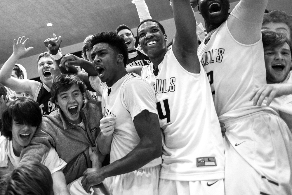 St. Pauls High School players (from left to right) Tre Hamer, Ryan Lee, and Iba Camara collide with fellow students after winning the MIAA B Conference Championship at UMBC RAC on Feb. 16, 2014.