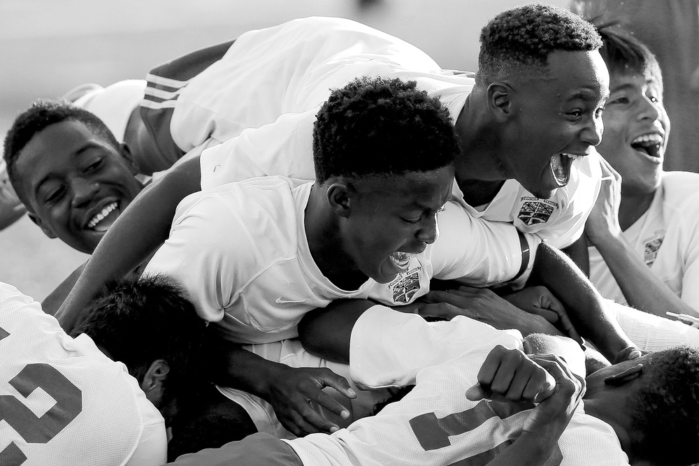 Members of the Landsdowne boys soccer dog piles on top of Jermaine Desoto after he scored the game winning goal in double overtime during a game against Overlea on Sept. 23, 2014 in Landsdowne, Maryland.