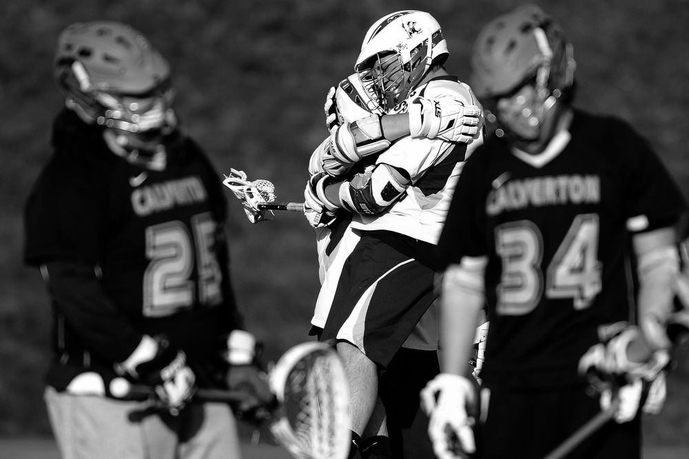 Brett Altenburg, second from left, of Mount Saint Joseph's celebrates with teammate Sam Sears after Sears scores during a boy's lacrosse game in Baltimore, Maryland on April 17, 2014.